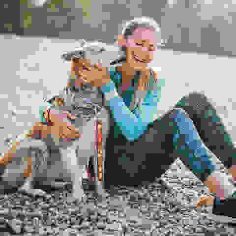 Eine Frau kuschelt nach dem Sport mit ihrem Hund