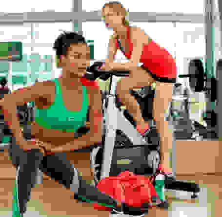 2 Frauen trainieren in einem Fitnessstudio. Sie tragen grüne Sport-BHs und Sport-Tights.