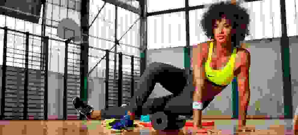 Eine Frau trainiert in einem Fitnessstudio mit einer Faszienrolle. Sie trägt dabei eine blaue Trainingshose und einen neongelben Sport-BH von Nike.