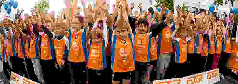 Viele Kinder strecken beim Stadtlauf Augsburg die Hände in den Himmel.