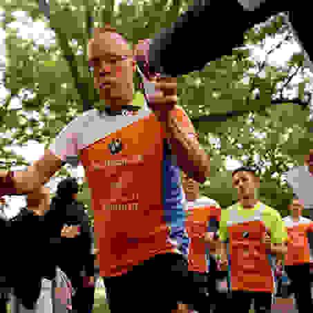 Ein Läufer bekommt während des Laufens beim Stadtlauf Hamburg einen Becher mit Wasser gereicht.