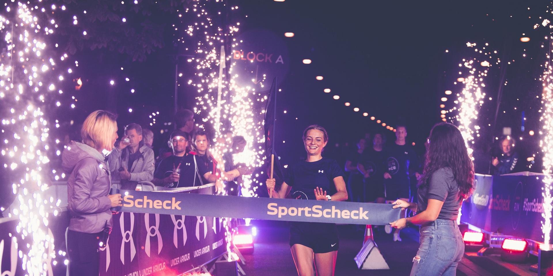 Die Gewinnerin des SportScheck Runs Magdeburg läuft ins Ziel ein.