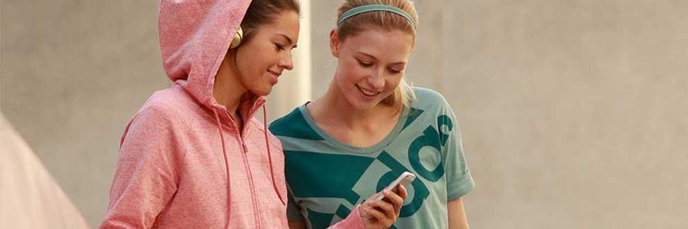 2 Frauen in unterschiedlichen Sportoutfits schauen sich gemeinsam etwas auf dem Handy an.