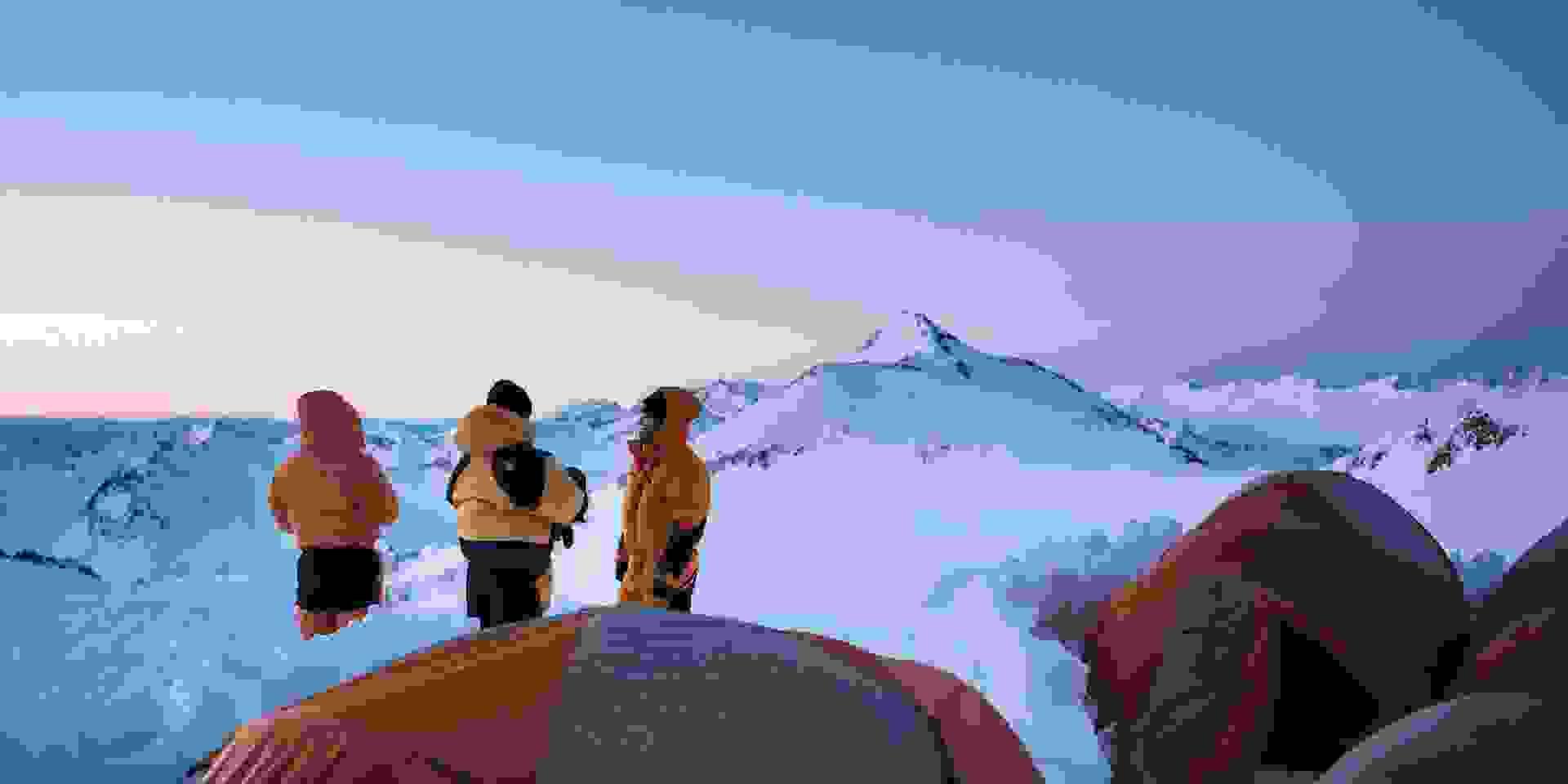 Drei Hochtouren-Geher stehen bei Sonnenuntergang vor dem Eingang der Zelte ihres Hochlagers