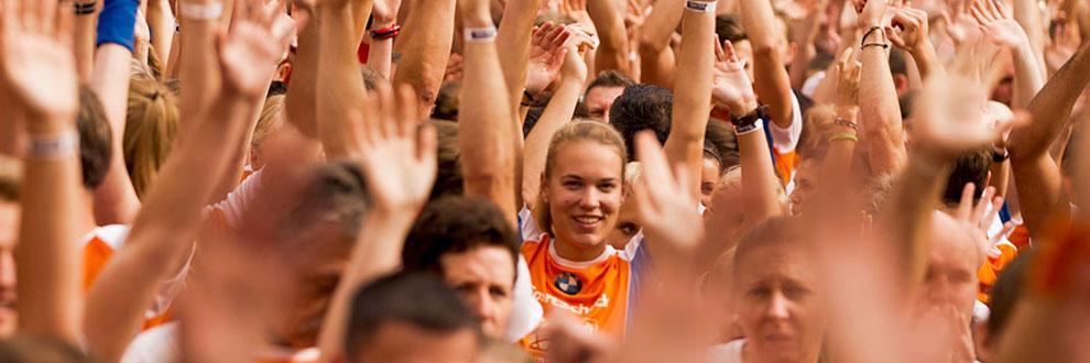 Viele Teilnehmer strecken ihre Arme in die Luft, eine Läuferin schaut direkt in die Kamera beim Stadtlauf in Braunschweig.