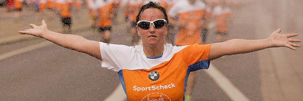 Eine Läuferin streckt die Arme seitlich vom Körper weg während eines Dresden Stadtlaufs bei Regen.