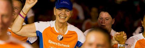 Eine Frau streckt den Arm in die Höhe und lächelt beim Zieleinlauf vom Stadtlauf Hannover.