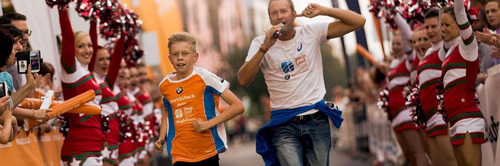 Ein junger Teilnehmer läuft die Zielgerade beim SportScheck Stadtlauf Magedeburg entlang. Hinter ihm läuft ein Moderator mit Mikrofon in der Hand.