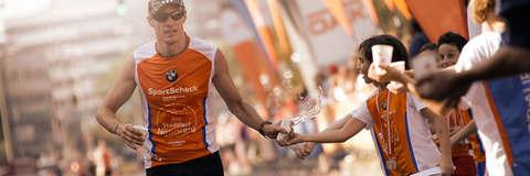 Ein Läufer beim Nürnberg Stadtlauf nimmt Becher mit Wasser während des Laufens entgegen.