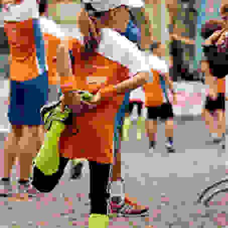 Ein junges Mädchen beim Dehnen der Oberschenkelmuskulatur kurz vor Beginn des Braunschweiger Stadtlaufs.