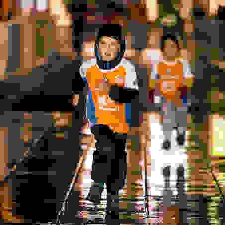 Ein kleiner Junge läuft durch den Regen während des Stuttgart Stadtlaufs für Kids.