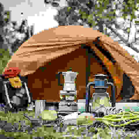 Ein gelbes Zelt vor dem verschiedene Outdoor- und Camping-Utensilien stehen.