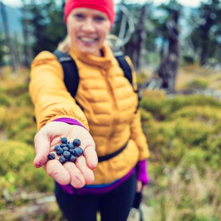 Eine Frau hält eine Handvoll Beeren in Richtung Kamera.