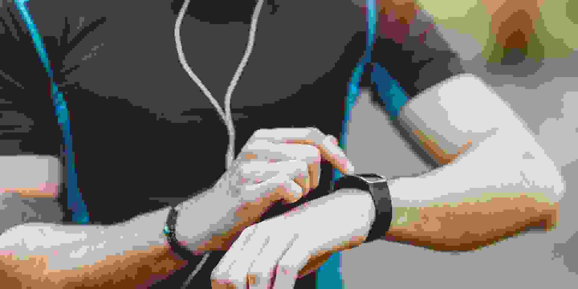 Ein Trailrunner im blauen Shirt kontrolliert seine Laufleistung auf seiner Fitnessuhr.