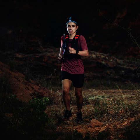 Ein Trailrunner läuft im Dunkeln mit einer Stirnlampe über eine Bergwiese.