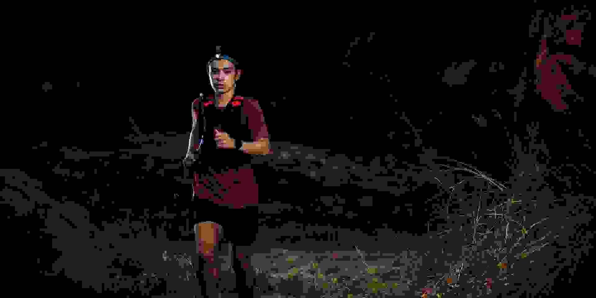 Ein Trailrunner während des Laufens von vorne im Dunkeln fotografiert.