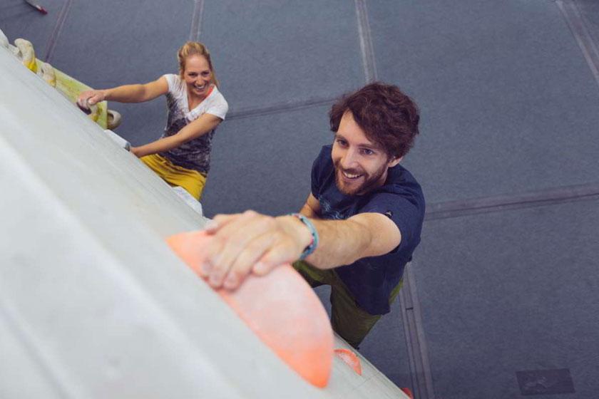 Ein Mann und eine Frau bouldern an einer Kunstwand in einer Boulderhalle. Sie sind von oben fotografiert.