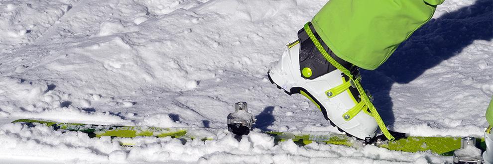 Ein Tourenskischuh und die Bindung an einem Tourenski im Schnee in der Nahaufnahme.