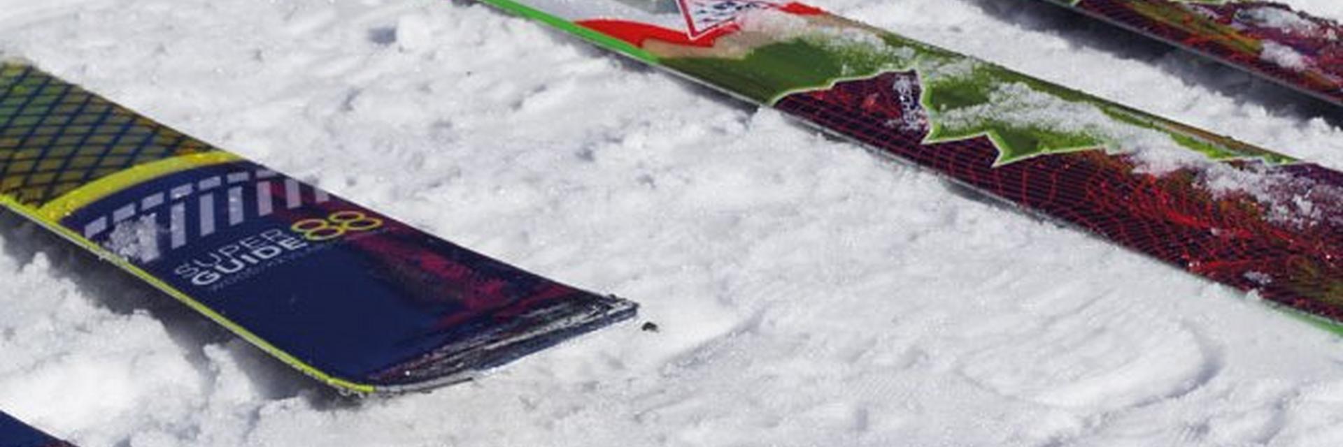 Diverse Tourenski, die im Schnee liegen.
