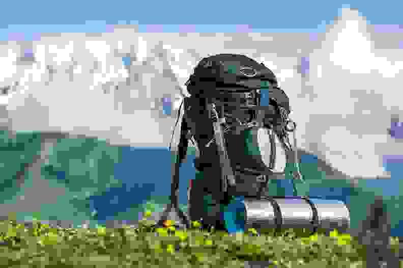 Ein Rucksack steht auf einer Wiese. Im Hintergrund ist ein Bergpanorama zu sehen.