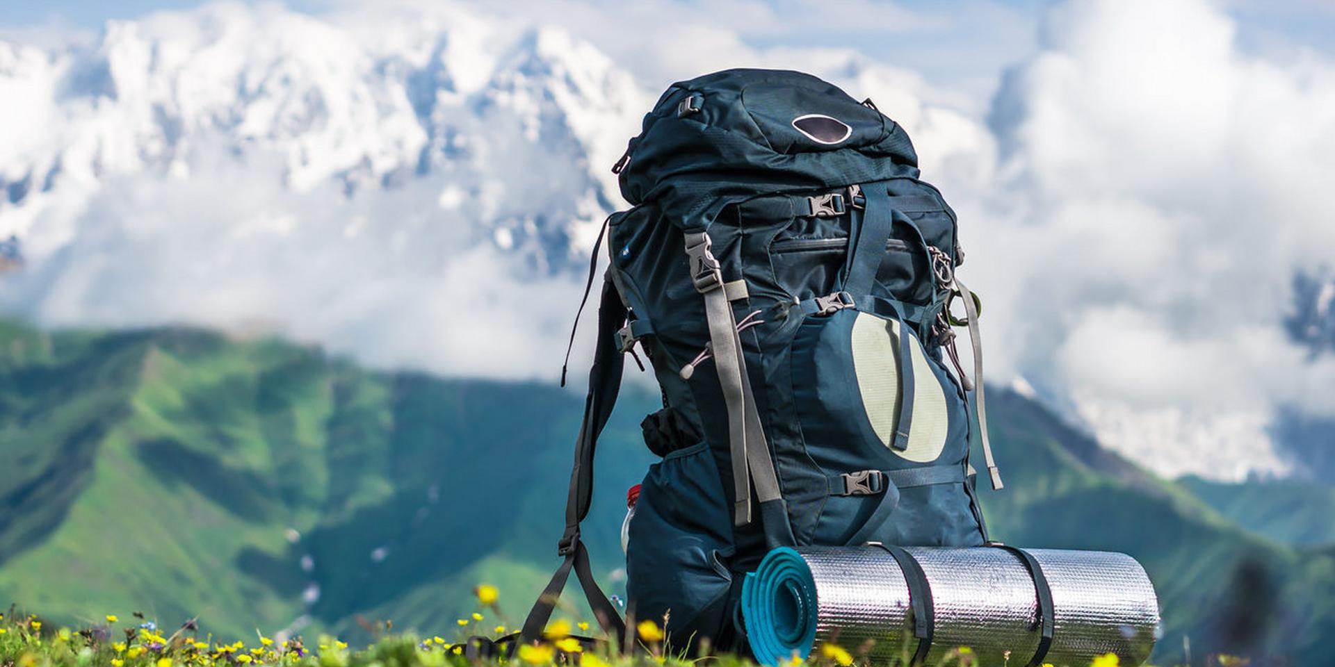 Was steht alles auf deiner Packliste? Ein Rucksack, Handschuhe, Kompass und Sonnenbrille auf einem Holztisch.