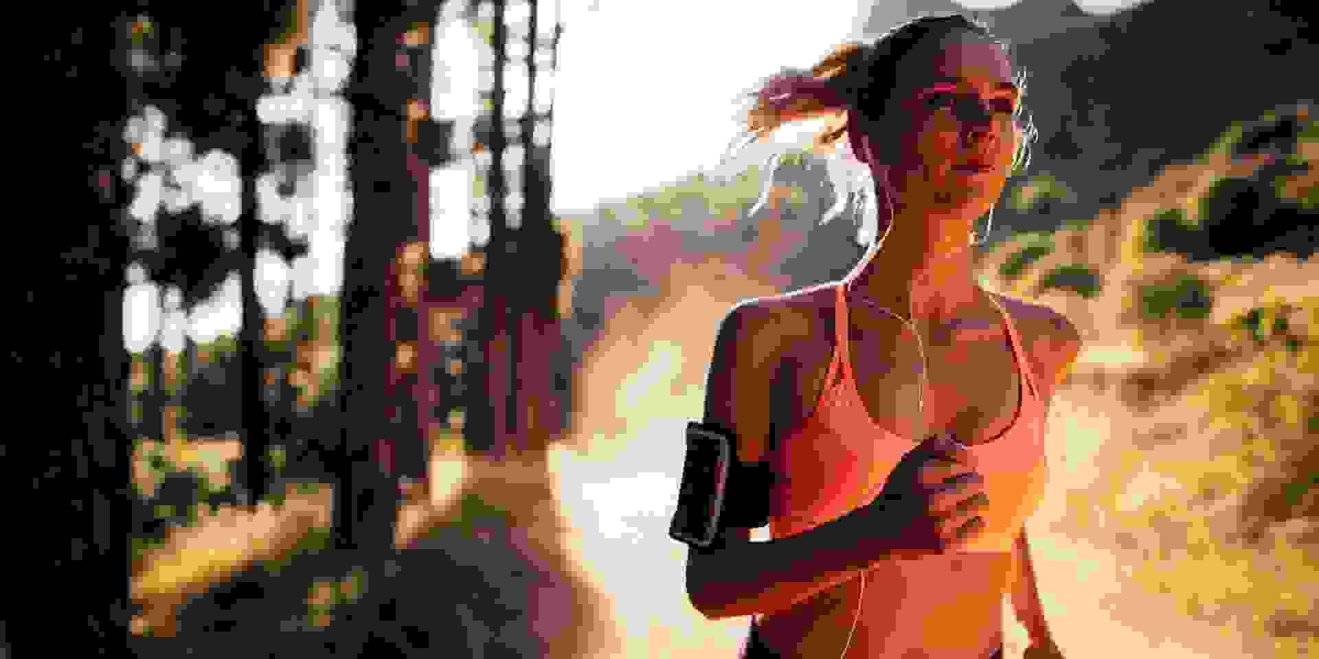 Eine Frau trackt ihre Geschwindigkeit beim Trailrunning mit dem Smartphone