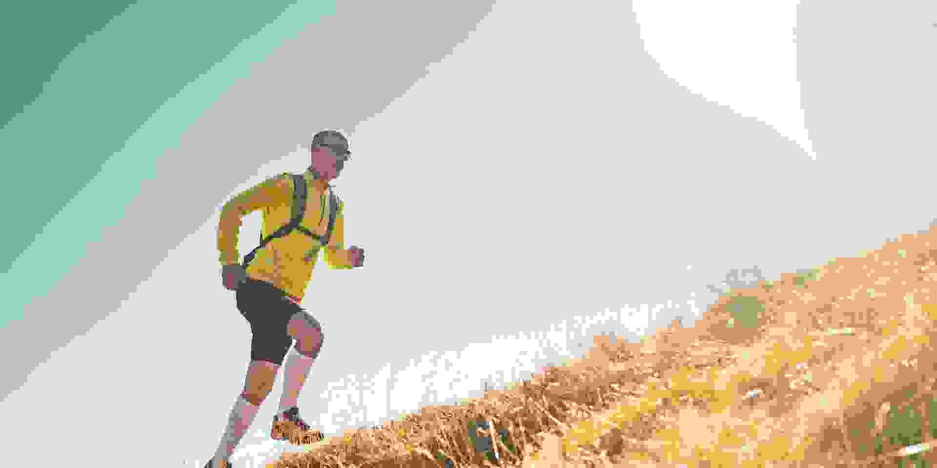 Ein Mann in schwarzer kurzer Hose und gelbem Trainingsshirt läuft beim Trailrunning eine Bergwiese hinauf.