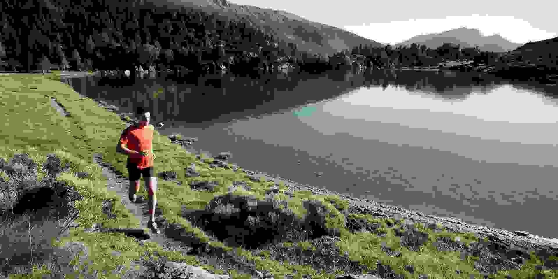 Ein Trailrunner läuft an einem Bergsee entlang.