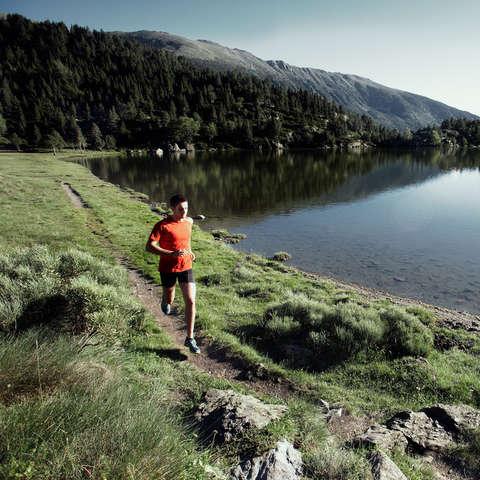 Ein Mann beim Trailrunning am Ufer eines Bergsees.