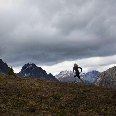 Eine Trailrunnerin läuft ber regnerischem Wetter über eine Bergwiese.