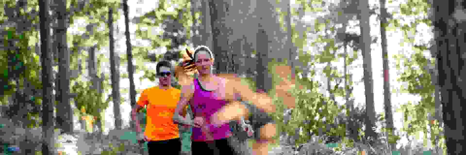 Ein Mann und eine Frau beim Trailrunning im Wald.