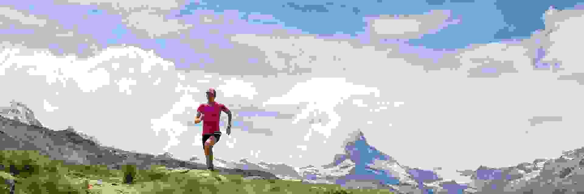 Eine Trailrunnerin läuft einen Trail während das Matterhorn im Hintergrund ist.