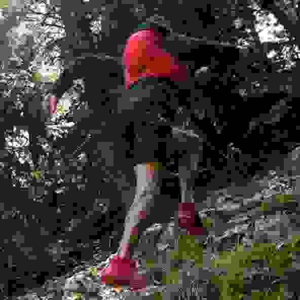 Ein Läufer läuft mit Trailrunning Schuhe und Rucksack einen steilen Waldweg hinauf.