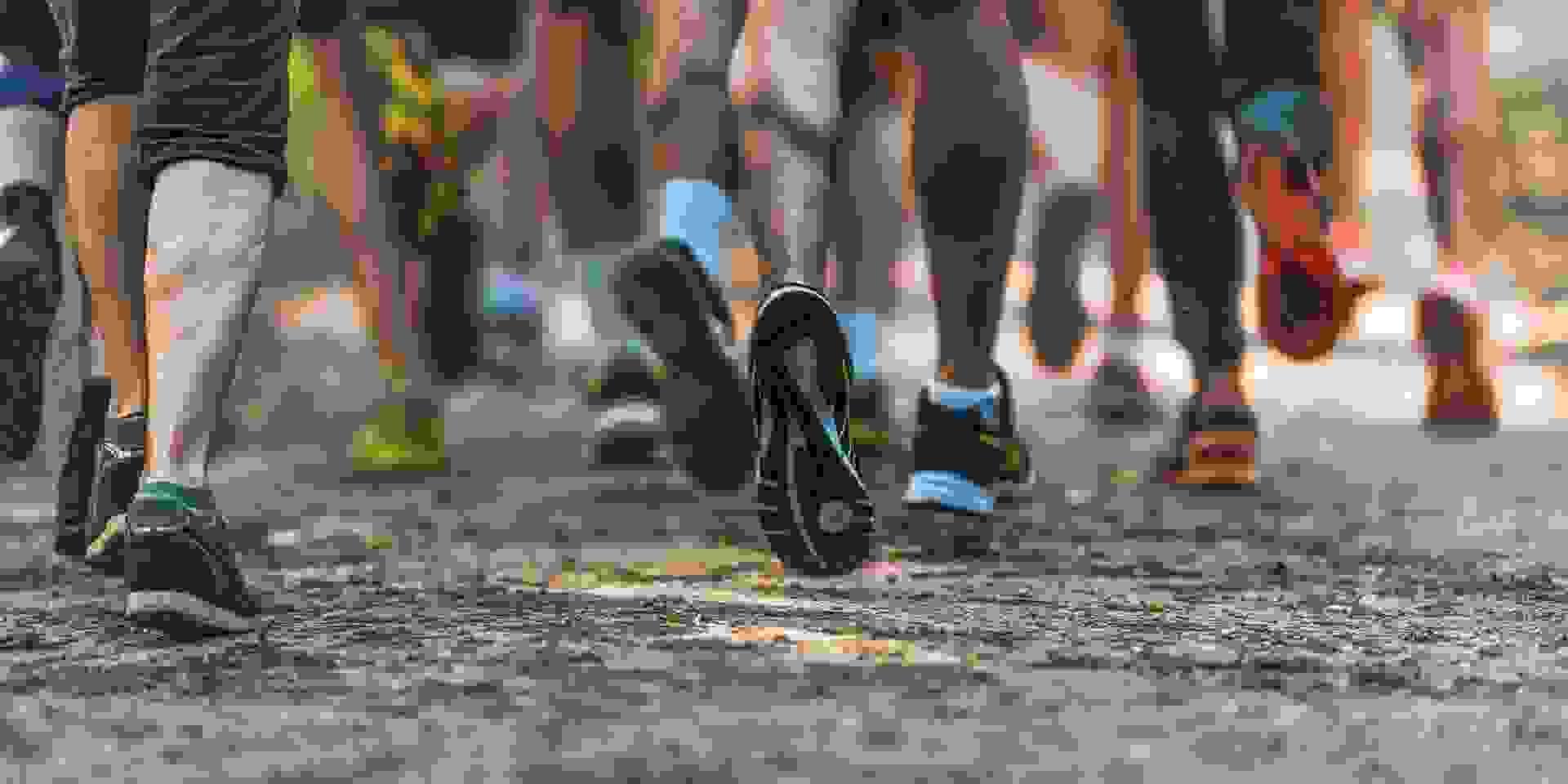 Läufer laufen auf einem Feldweg nebeneinander her. Zu sehen sind die Unterschenkel und Füße, die in unterschiedlichen Laufschuhmodellen stecken.