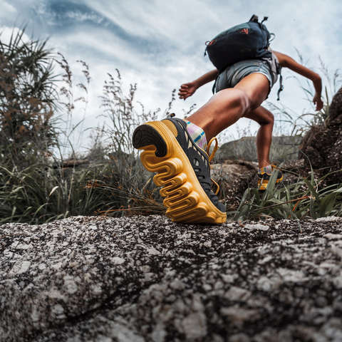Eine Trailrunnerin mit gelben Trailrunningschuhen läuft über steinigen Untergrund.