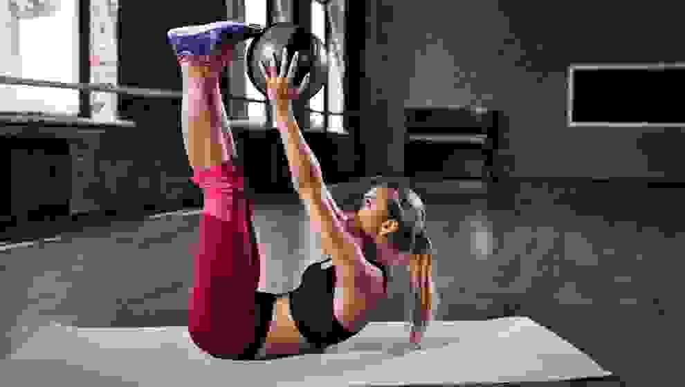 Eine Frau trainiert mit einem Ball auf einer Fitnessmatte.