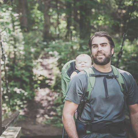 Ein Vater hat sein kleines Kinder mit einer Kraxe auf den Rücken geschnallt.