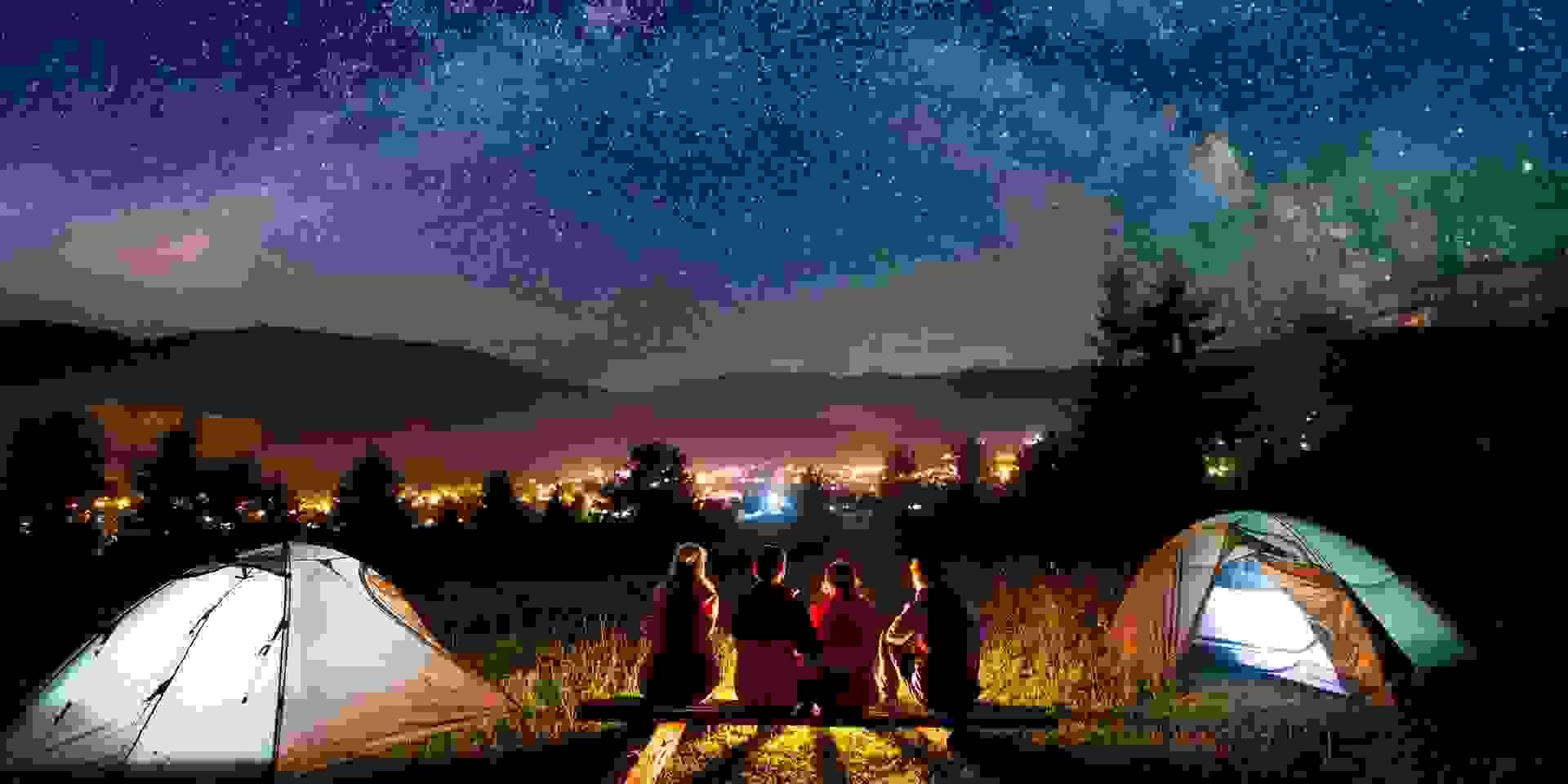 Zwei Frauen und zwei Männer hocken zwischen ihren Zelten und schauen in einen Sternenhimmel am Rande einer Stadt.