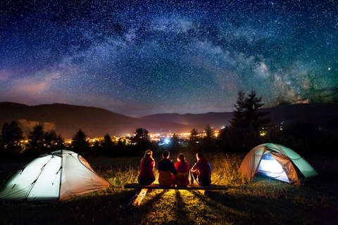 2 Jungs und 2 Mädchen sitzen vor ihrem grünen Zelt und genießen den Sternenhimmel mit Blick auf die Lichter einer Stadt.