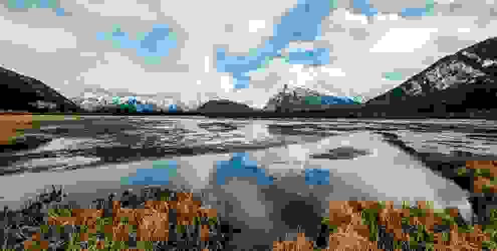Eine wunderschöne Landschaftsaufnahme aus Kanada, die zum Wandern einlädt. Im Hintergrund sind verschneite Berge zu sehen.