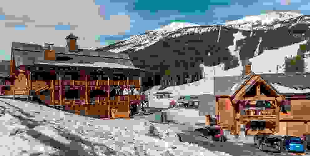 Ein großes Holzhaus umgeben von Schnee. Kanada ist ideal für Wintersportler.