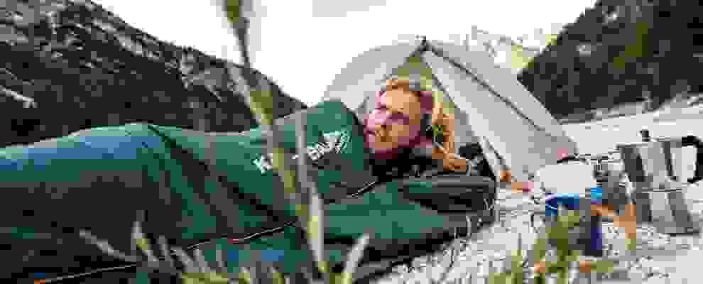 Ein Mann liegt auf einer Isomatte und in einem Schlafsack vor seinem Zelt.