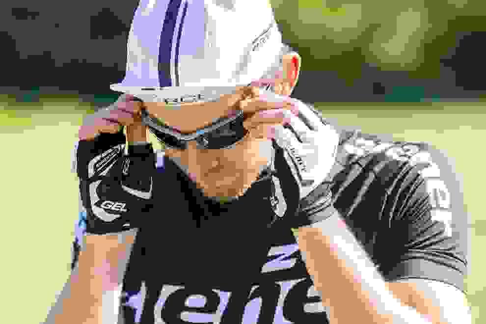 Ein Radfahrer in Nahaufnahme. Er trägt einen Fahrradhelm und Fahrradtrikot von ZIENER in schwarz/weiß. Dazu passende ZIENER Fahrradhandschuhe und eine Sonnenbrille.