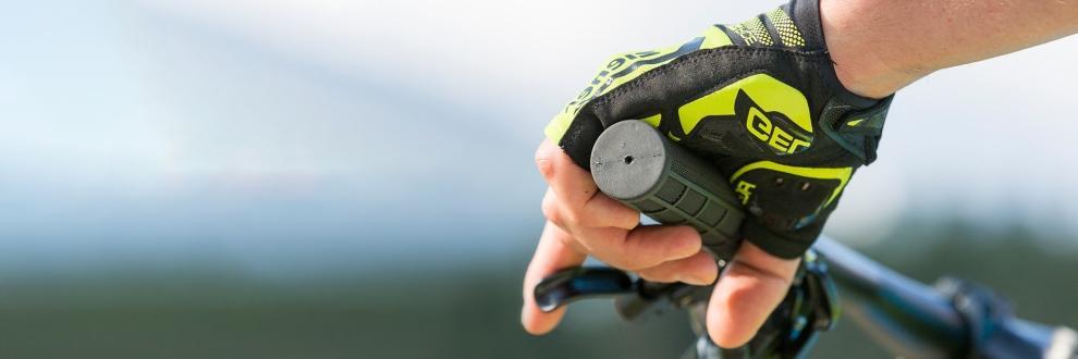 Eine Hand, die in einem ZIENER Fahrradhandschuh steckt und den Griff eines Fahrradlenkers umklammert.