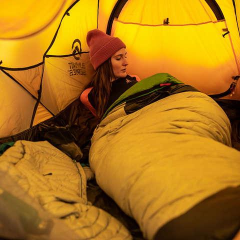 Eine Frau liegt im Zelt in einem warmen Schlafsack