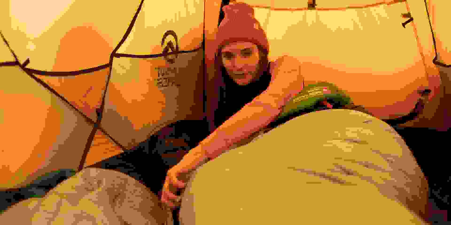 Eine Frau liegt im Zelt in einem warmen Daunenschlafsack