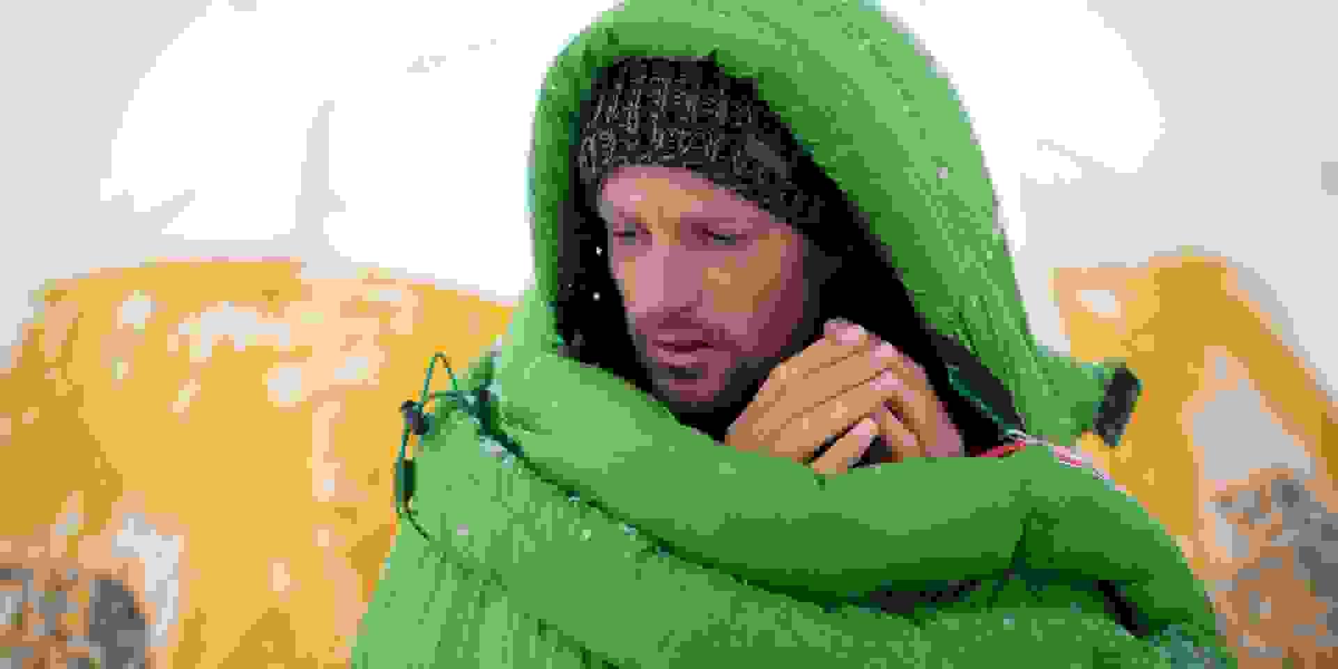 Ein Mann steht in verschneiter Landschaft in einem sehr warmen Schlafsack vor seinem Zelt