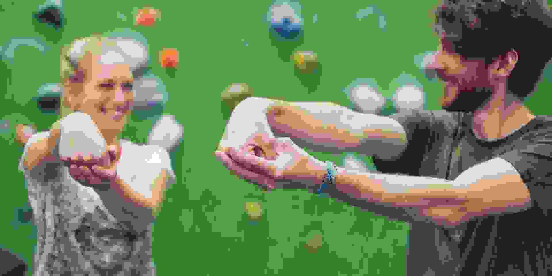 Ein Mann und eine Frau wärmen sich für das Bouldern auf. Dafür strecken sie einen Arm nach vorne aus, winkeln die Faust nach unten ab und ziehen diese mit der anderen Hand an den Körper.