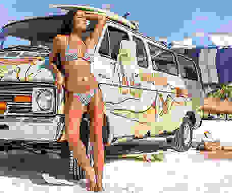 Eine Frau lehnt in einem bunten Bikini an einem Multivan, der mit Graffitis bemalt wurde.