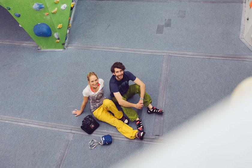 Ein Mann und eine Frau sitzen mitten in einer Boulderhalle auf dem Fussboden. Sie tragen lockere und bunte Boulderkleidung.